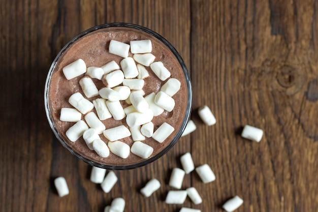 Вид сверху на горячий шоколад, смузи или коктейль, посыпанный зефиром