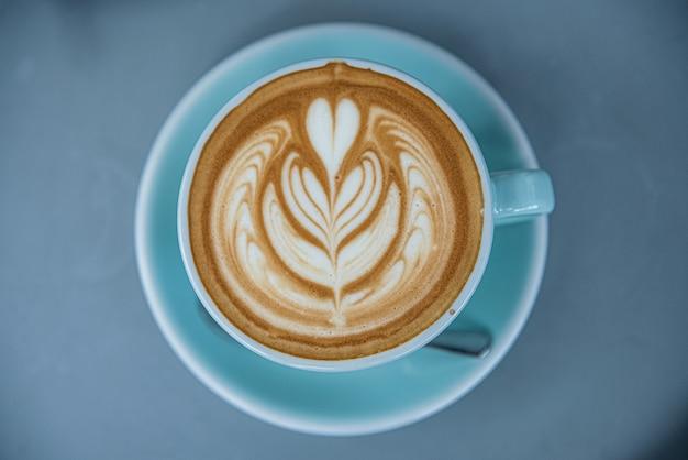 青いカップでホットコーヒーカフェラテのトップビュー