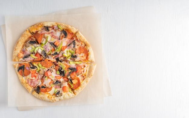 Вид сверху горячей вкусной традиционной итальянской целой пиццы с помидорами, грибами, мясом и сыром