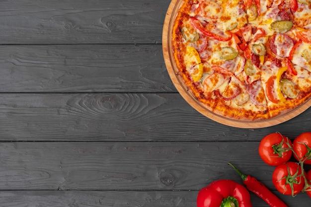 黒い木製のテーブルの上の熱いピザの上面図