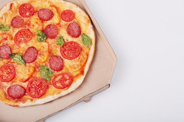 ハムとボックスで熱いおいしいピザの平面図スライスし、白いテーブルで提供しています、クローズアップ表示。ファーストフード、ジャンクフード、健康的な食事のコンセプト