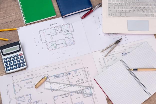 Вид сверху на план дома с ноутбуком, калькулятором и карандашами
