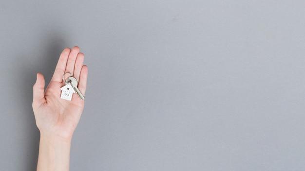 Вид сверху человеческой руки, держащей ключ от дома на сером фоне