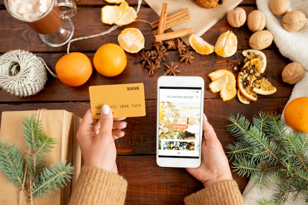 プラスチック製のカードとスマートフォンで人間の手の上面にクリスマスプレゼント、針葉樹、フルーツの木製テーブルの上