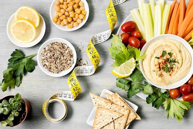 Вид сверху хумуса с ассортиментом овощей и измерительной ленты