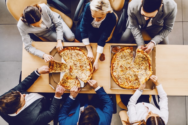 테이블에 앉아 점심 피자를 먹고 배고픈 동료의 상위 뷰. 기업 회사 인테리어.