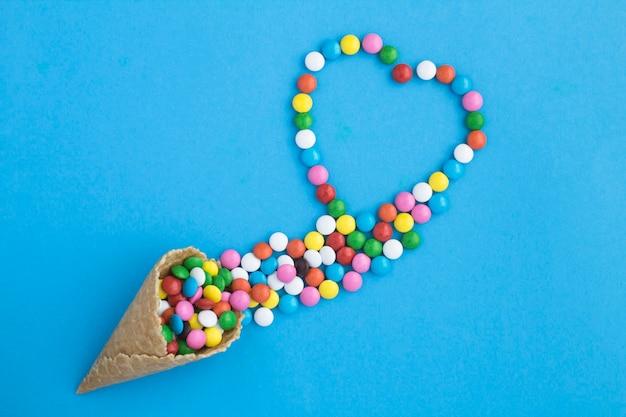 Вид сверху мороженого с красочными конфетами на синем фоне