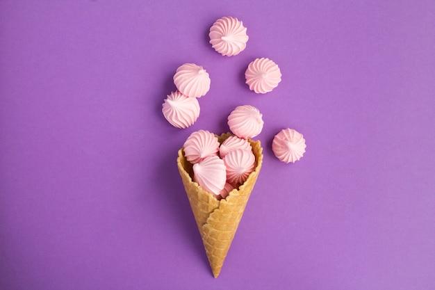 紫の背景の中央にピンクのメレンゲとアイスクリームコーンの上面図