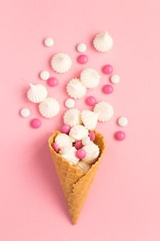 ピンクのテーブルに白いメレンゲとキャンディーとアイスクリームコーンの上面図。