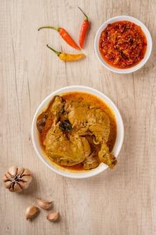 Вид сверху традиционной индонезийской кухни аям гулай паданг аям гулай - популярное блюдо из куриного карри из паданга, западная суматра.