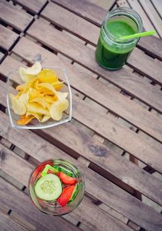 屋外の木製テーブルの上に注入されたフルーツウォーターカクテルと緑の野菜のスムージーの上面図。健康的なオーガニックサマードリンクのコンセプトです。