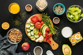 Top view of ingredients; dryfruits and vegetables on black background