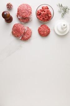 ハンバーガーを作るための食材の平面図。大理石のテーブル、肉入りのガラスのボウル、
