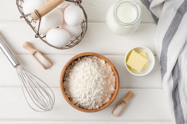 白い木製のテーブルで伝統的な薄いパンケーキやクレープを作るための材料のトップ ビュー