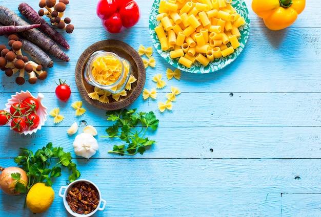 木材の背景上のスパゲッティのイタリア食材の平面図です。