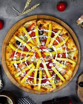 フライドポテトをトッピングしたイタリアのピザのトップビュー