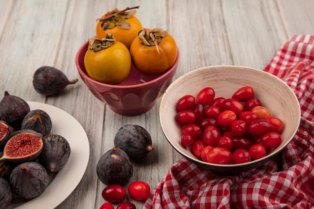 灰色の木製の背景に柿の果実とチェックの布の上のボウルにコーネリアチェリーと白いプレート上のジューシーな黒いミッションイチジクの上面図