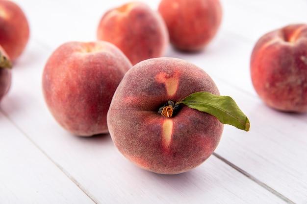 Вид сверху сочных вкусных и свежих персиков с листьями, изолированными на белой поверхности