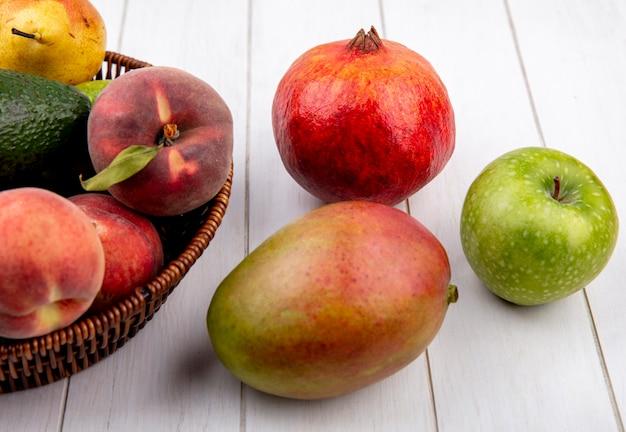 白い表面に分離されたアップルマンゴーとバケツに桃の梨などのジューシーなフルーツのトップビュー