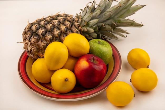 Вид сверху сочных фруктов, таких как ананас, разноцветных яблок и лимонов на миске с лимонами, изолированной на белой стене