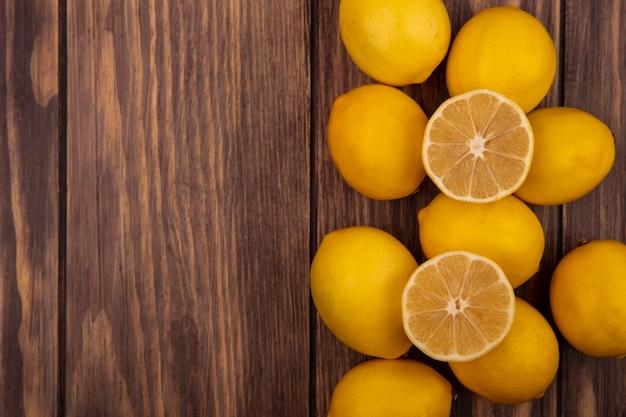 コピースペースのある木製の壁に分離されたジューシーな半分と全体のレモンの上面図