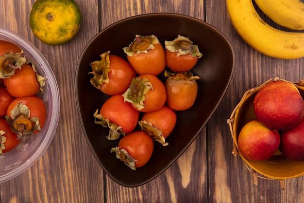 Вид сверху сочной хурмы на миске с персиками на ведре с бананами, изолированной на деревянной стене