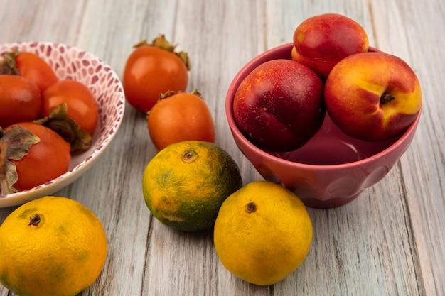 Вид сверху сочных мягких персиков на миске с хурмой и мандаринами, изолированными на серой деревянной стене