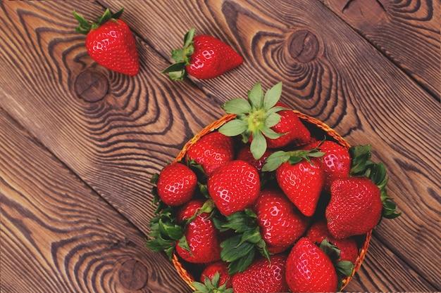 茶色のぼろぼろの素朴な木製テーブルの籐のボウルにジューシーなイチゴの上面図