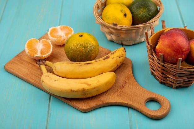 青い木製の壁のバケツに桃とバナナと木製のキッチンボード上のジューシーな全体と半分のみかんの上面図