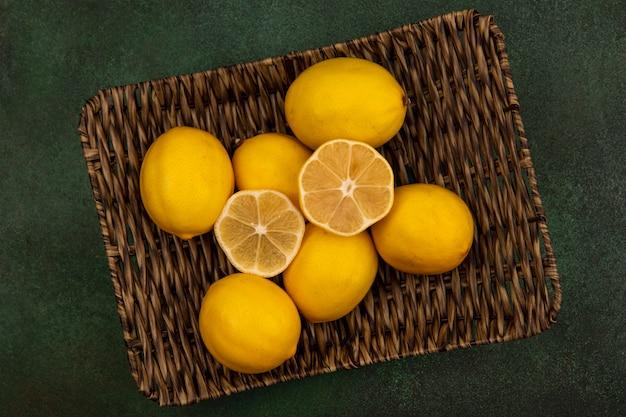 Вид сверху сочных желтых лимонов на плетеном подносе на зеленой стене