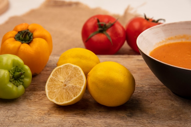 白い表面に分離されたカラフルなピーマンとボウルにレンズ豆のスープとジューシーな黄色のレモンの上面図