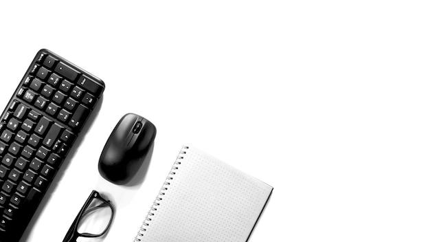 白い背景の上のキーボードマウスとメガネの上面図