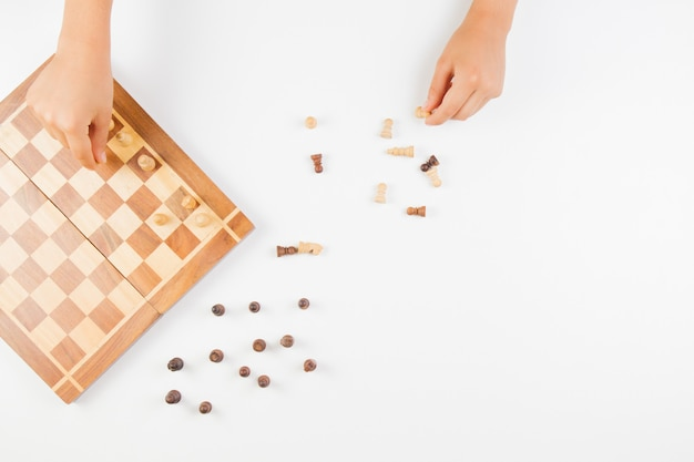 Вид сверху на детские руки и шахматная доска с шахматными фигурами