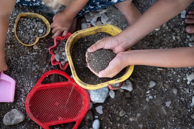 Вид сверху детей, играющих с песком, грязью и пластиковыми игрушками.