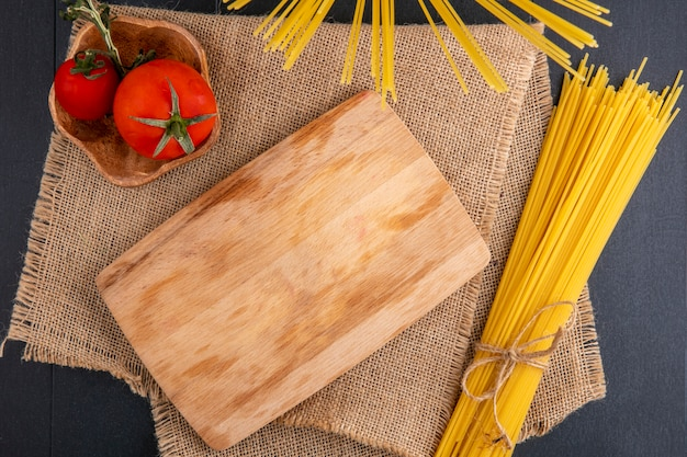 Вид сверху кухонной доски с сырыми спагетти и помидорами на бежевой салфетке на черной поверхности