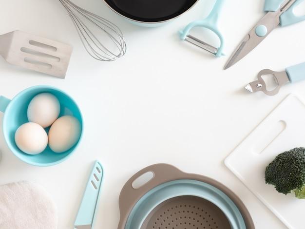 白いテーブル背景に台所用品、卵、野菜とキッチンルームのコンセプトのトップビュー。