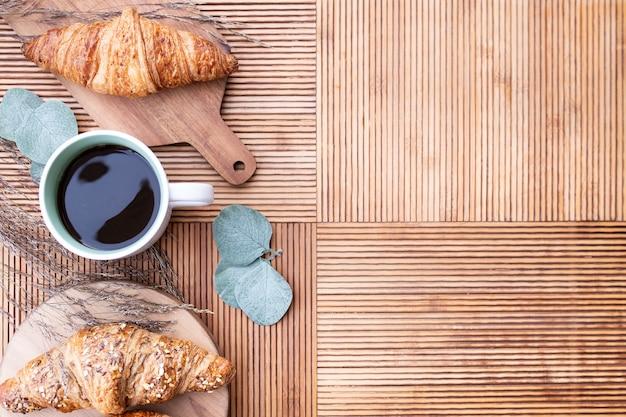 クロワッサンとユーカリの葉が付いたキッチンテーブルの上から見るコーヒーと右側のコピースペース