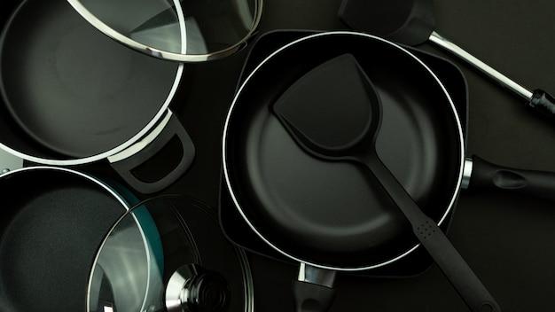 검은 가죽 백그라운드에 주방기구 팬 및 냄비의 상위 뷰.