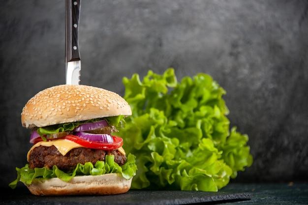 반 어두운 빛 표면에 검은 쟁반에 맛있는 샌드위치와 녹색의 칼의 상위 뷰