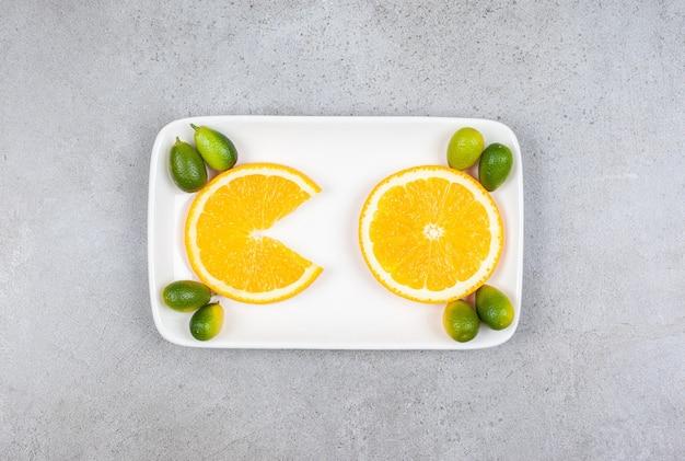 하얀 접시에 금귤과 오렌지 조각의 최고 볼 수 있습니다.