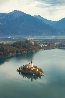 Вид сверху на озеро блед, остров с церковью и замок блед в осенний сезон