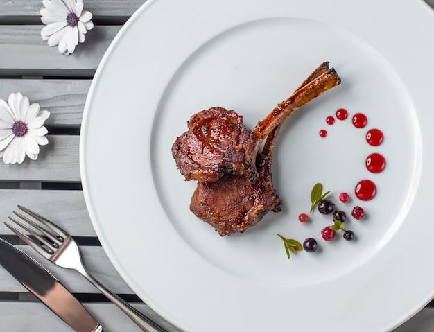 シロップドット装飾が施された白いプレートにラムリブステーキのトップビュー
