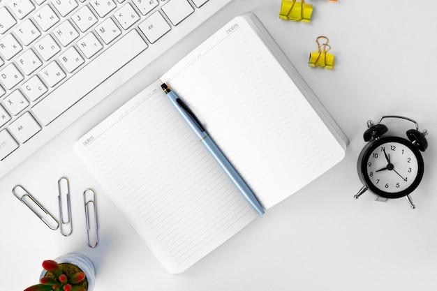 作業テーブル上のラップトップとメモ帳の上面図