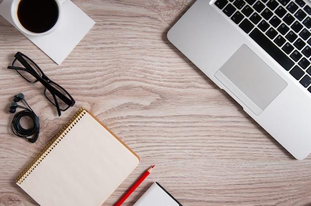 素朴な木製のデスクトップとコーヒーのカップにノートパソコンとメモ帳とメガネとヘッドフォンの平面図。