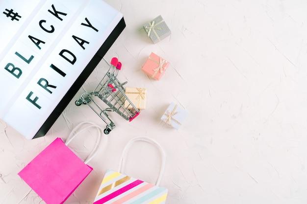 Взгляд сверху компьтер-книжки, слова продажи промотирования черной пятницы на лайтбоксе, подарочных коробках и тележке. плоская планировка