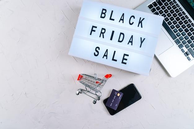 Взгляд сверху компьтер-книжки, слов продажи промотирования черной пятницы на лайтбоксе, смартфоне и карточках кредита. плоская планировка