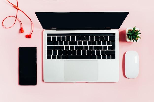 ラップトップ、コンピューターのマウス、携帯電話、ピンクのヘッドフォンの上面図