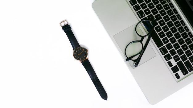 Вид сверху ноутбука, очков и часов на белом фоне пустого пространства