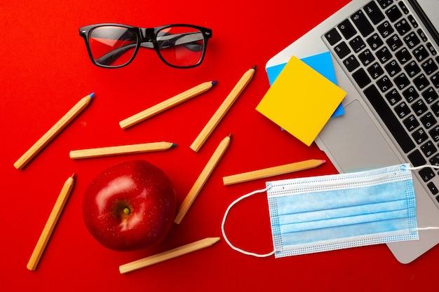 赤の背景にノートパソコンのキーボード、文房具、医療用フェイスマスクのトップビュー