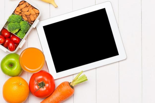 ノートパソコン、ガラスのオレンジジュース、職場でのプラスチック製の道具とランチボックスの新鮮なサラダの上面図